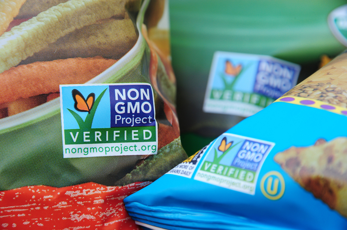 Labels on bags of snack foods indicate they are non-GMO food products.