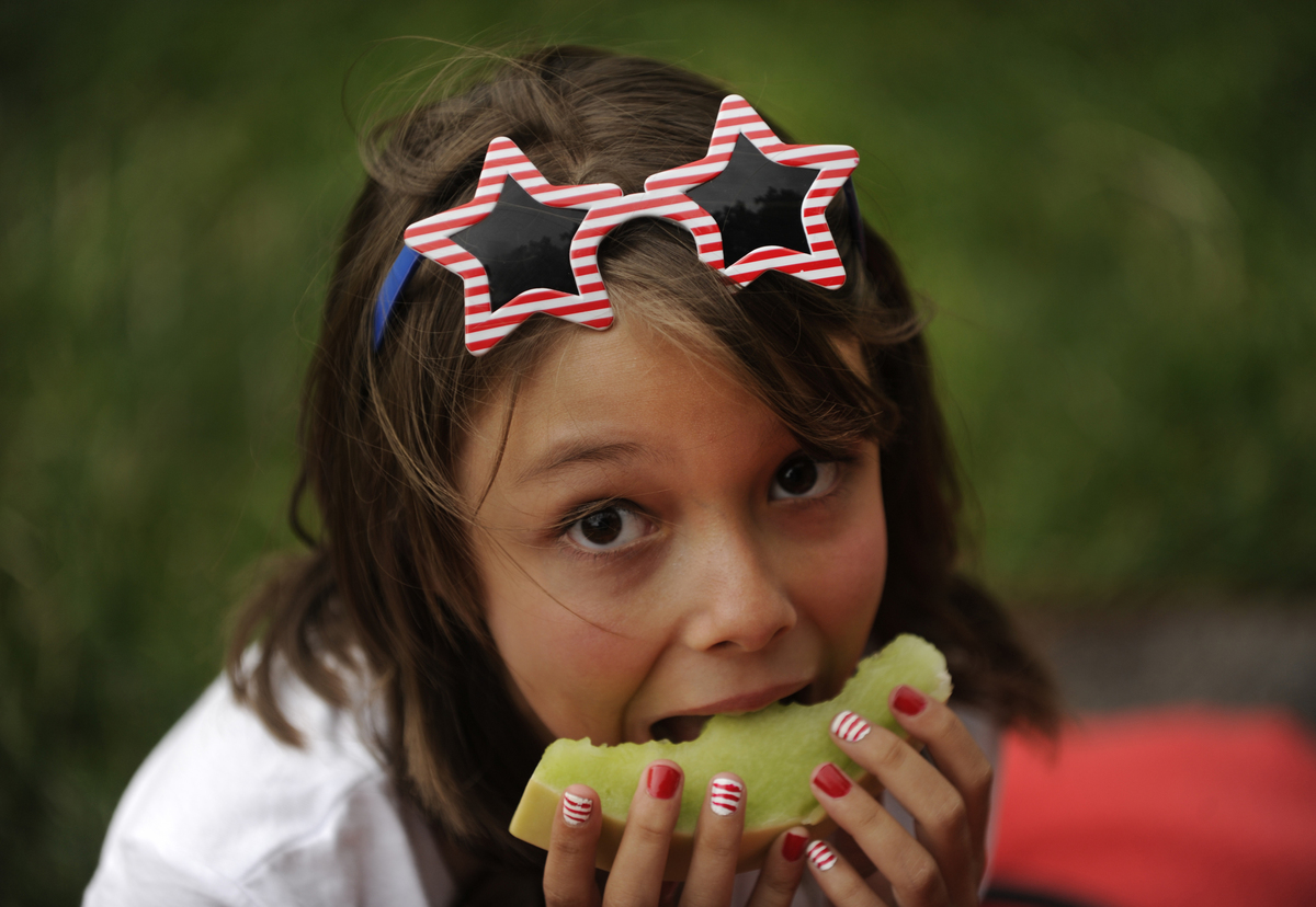 A young girl enjoys a picnic including honeydew melon while waiting for the Independence Day Eve show to start.