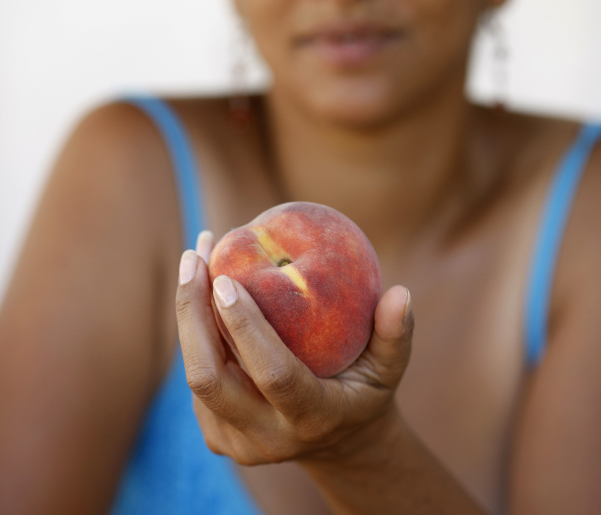 A woman holds a peach.
