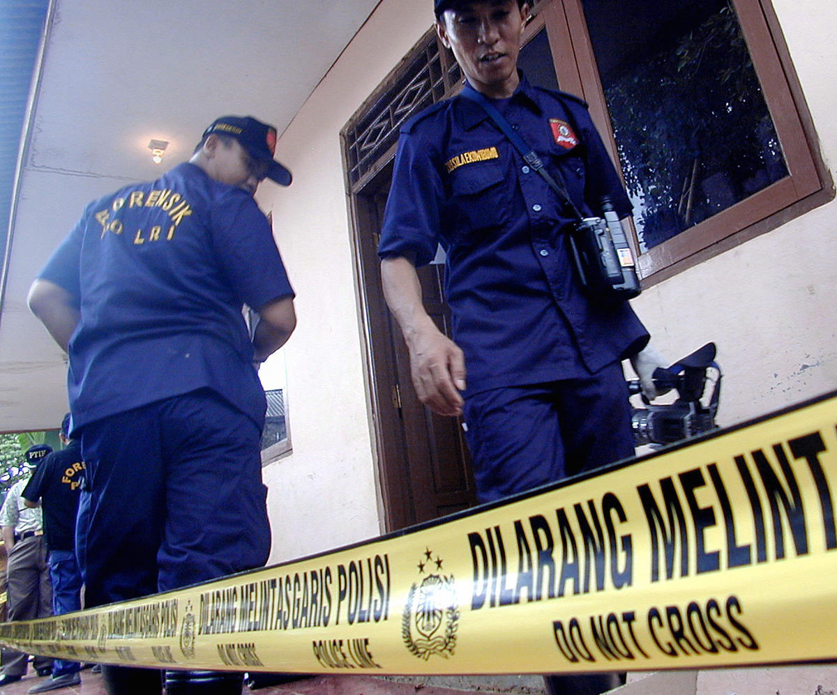 Forensic experts conduct an investigation near a house.