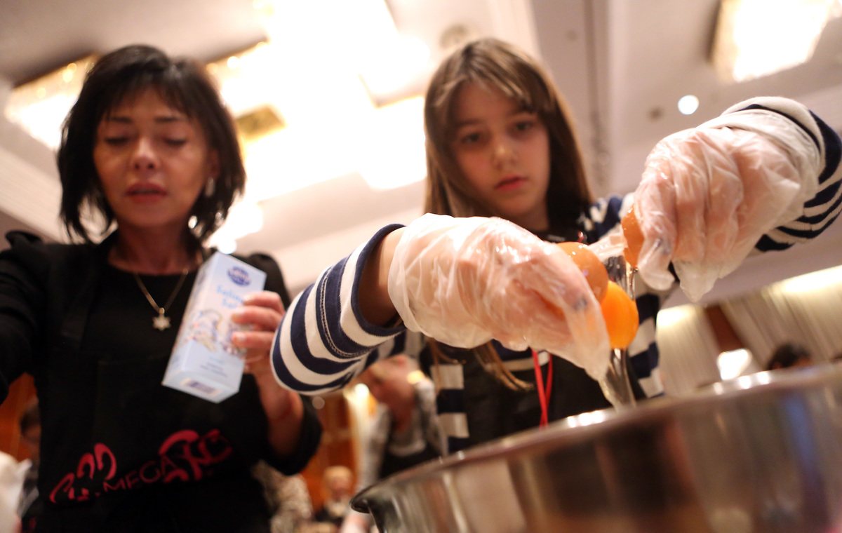 A young participant cracks an egg while making challah during the Mega Challah Bake.