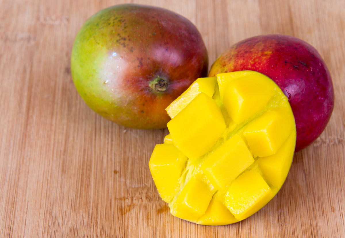 Imperfect mangoes with water droplets sit on the wooden surface of cutting board.