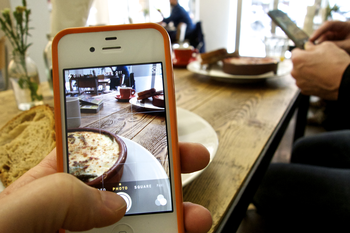 Two people photograph their food in a café with their smartphones.