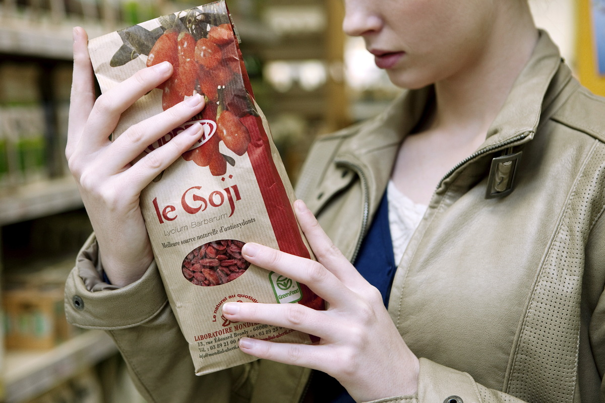 A woman holds a bag of organic dried goji berries in a supermarket.