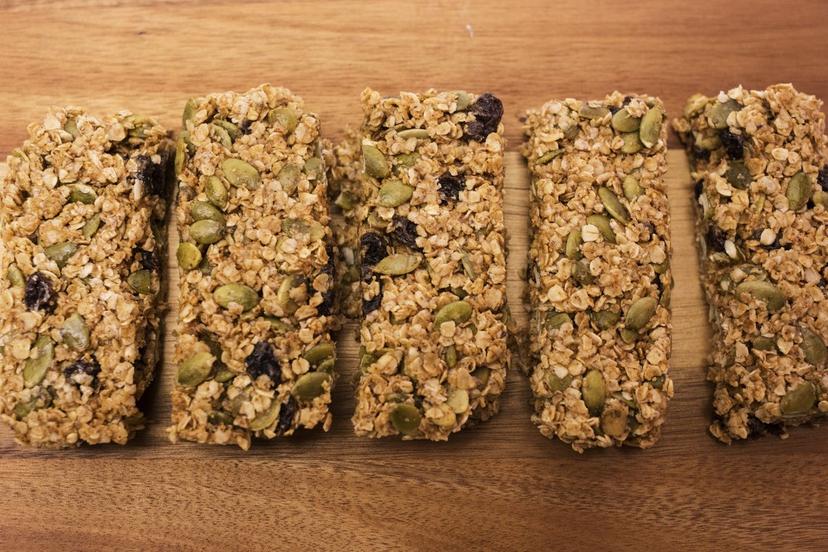 No-bake granola bars are lined up on a wooden cutting board.