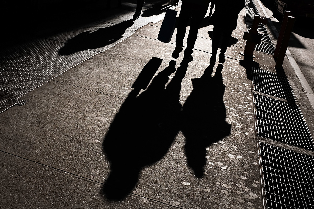 Shadows of people shopping in Manhattan are cast on the sidewalk.