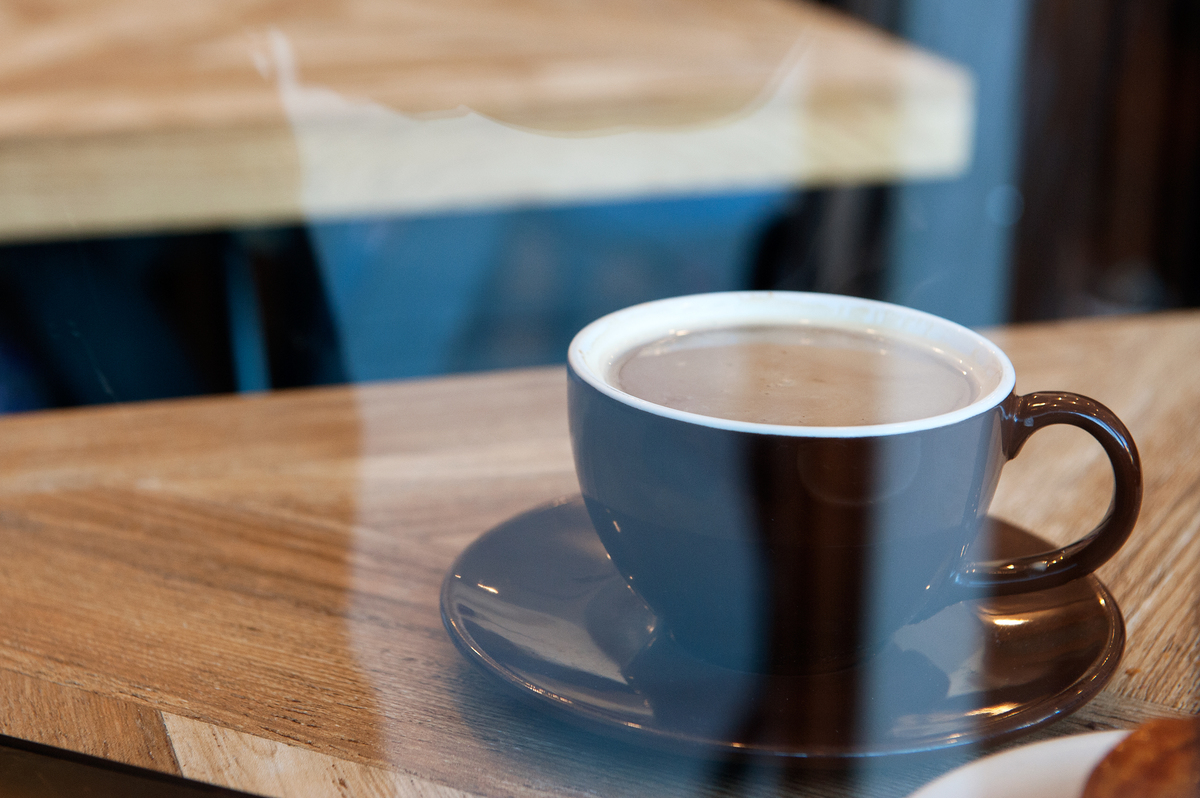 A cup of coffee sits on a table at Colson Patisserie.