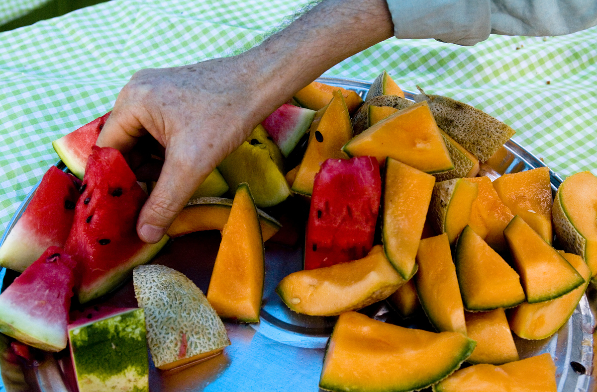 A man selects healthy fresh fruit for dessert from a tray of watermelon and cantaloupe.