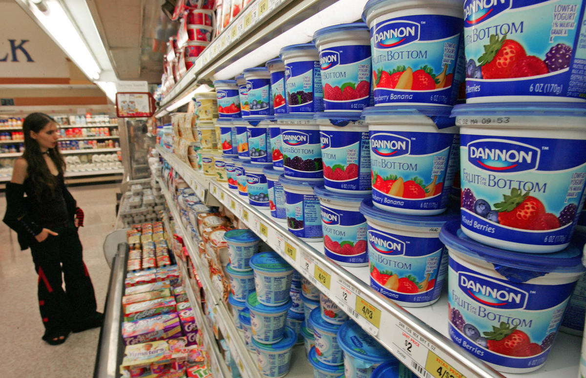 A customer shops for yogurt at a grocery store.
