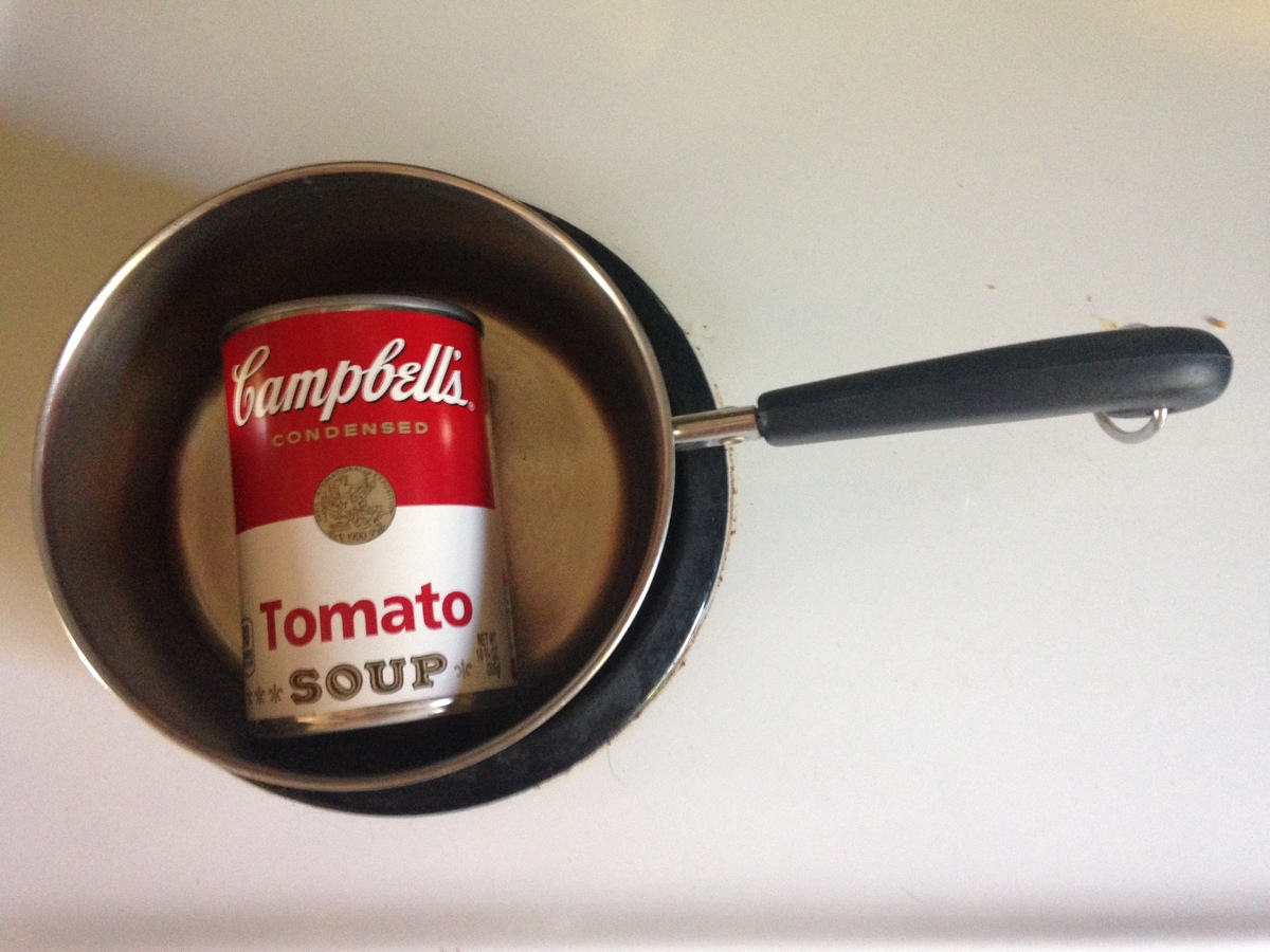A can of Campbell's Tomato Soup sits in a pot.