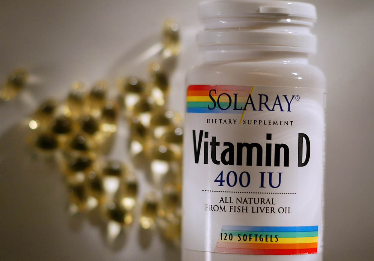 A bottle of vitamin D supplements stands in front of the pills.