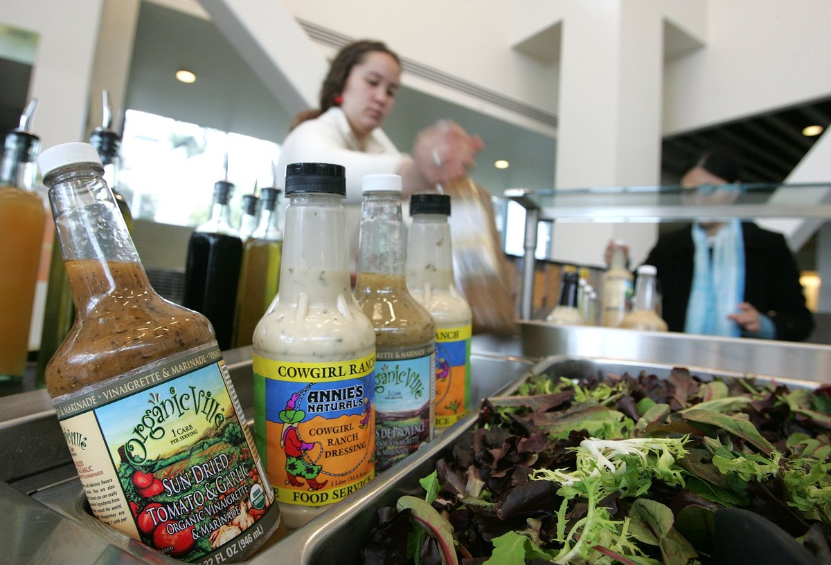 A student at the University of California, Berkeley pours organic salad dressing on a salad.
