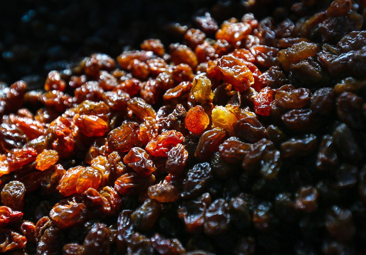 Raisins in a pile are illuminated.