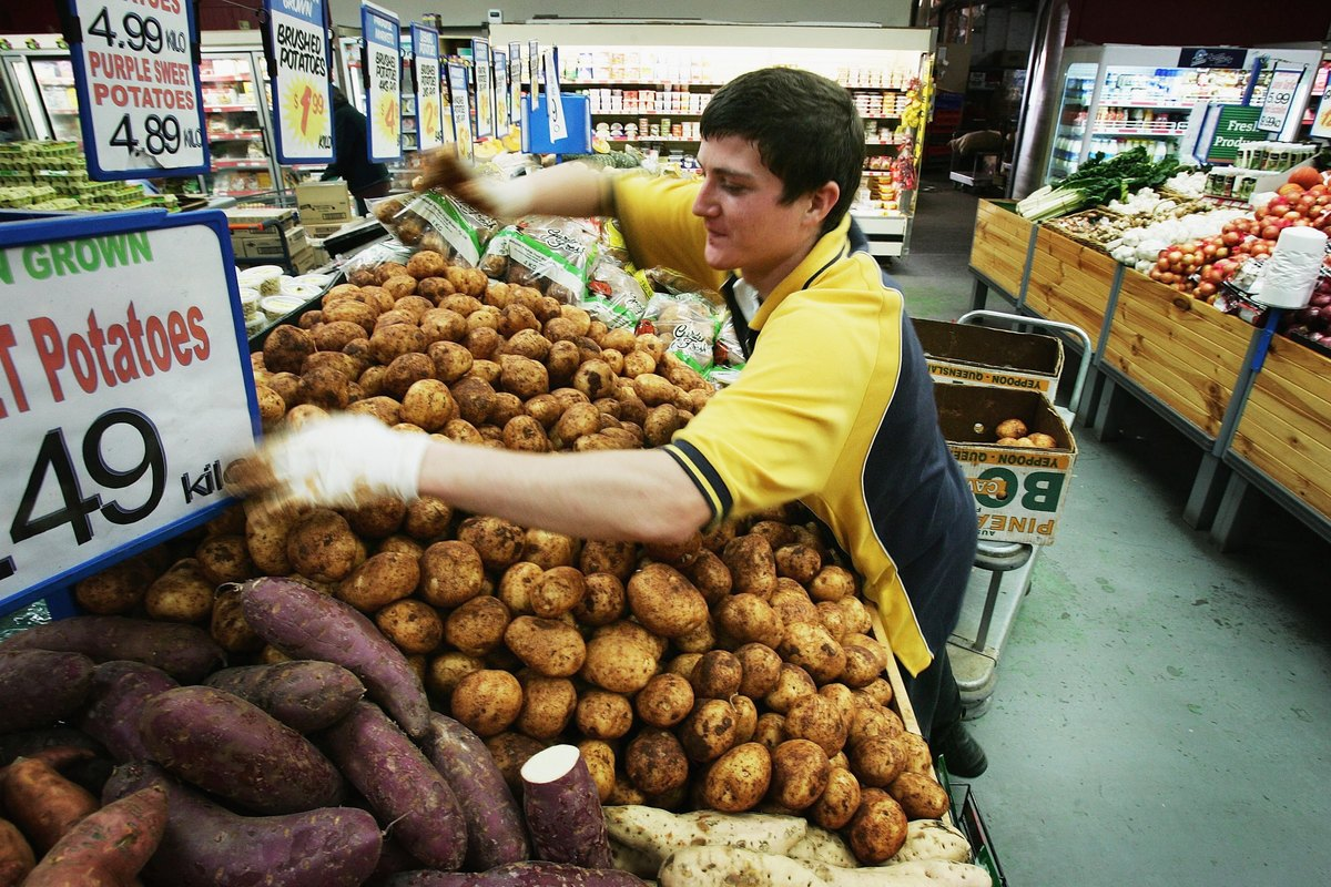 A supermarket employee stacks potatoes for sale.