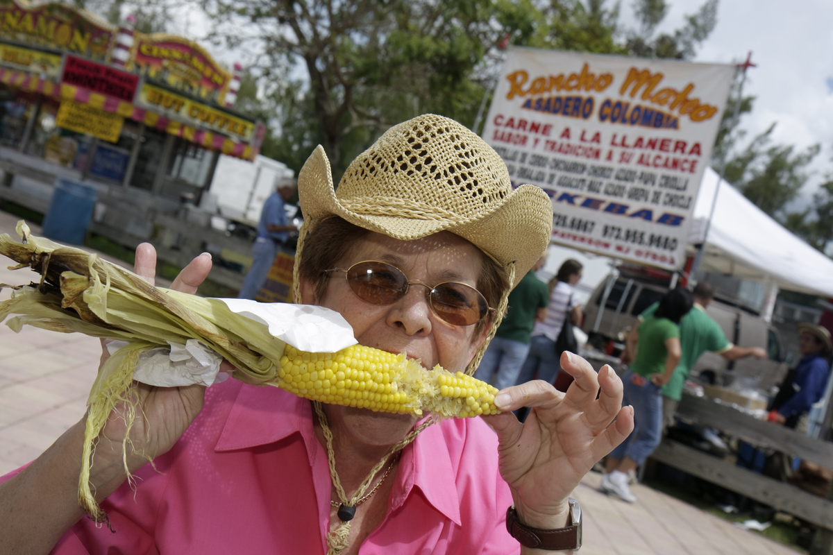 A senior woman eats a roasted corn on the cob at the Miami International Agriculture and Cattle Show.
