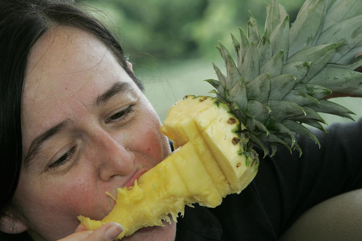 A Costa Rican enjoys a pineapple.