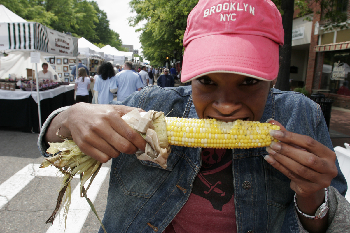 A woman eats a corn on cob at the Gosport Arts Festival.