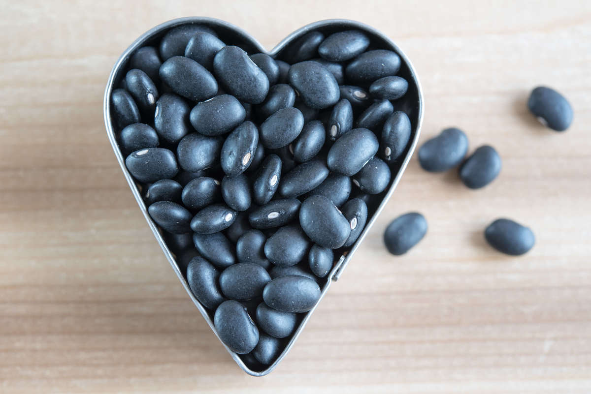 Raw, dried black beans are in a heart-shaped container.