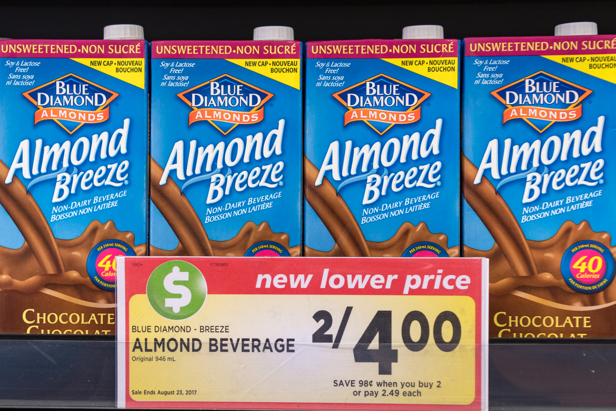 Diamond almond breeze beverage tetra packs are displayed on a rack with prices further reduced.
