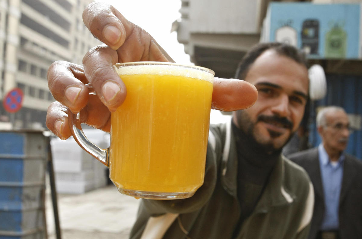 An Iraqi vendor serves a glass of fresh orange juice at his citrus fruit stand.