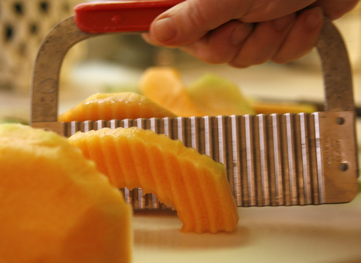 A person slices cantaloupe with a pickle cutter.