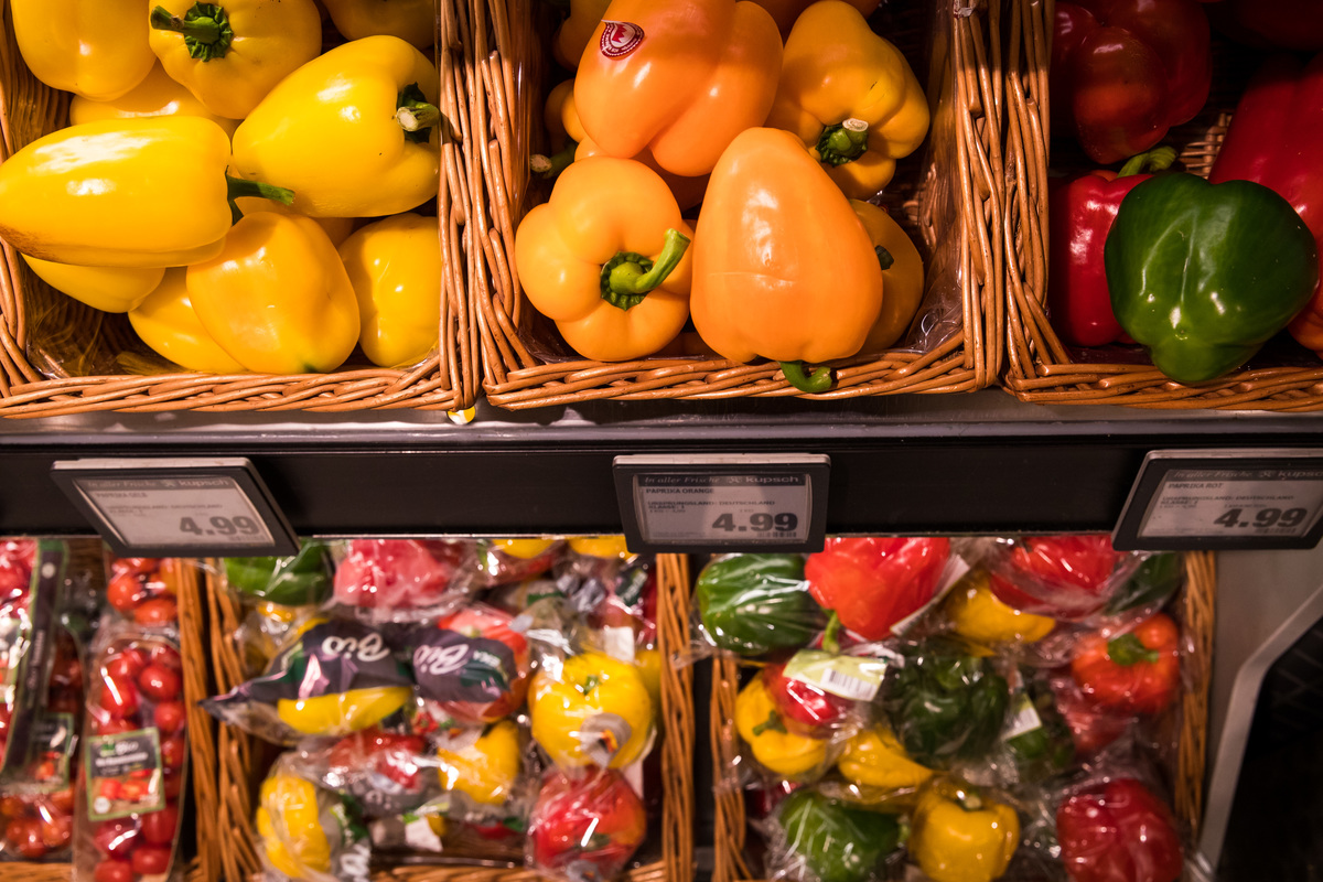 Bell peppers packaged in plastic and loose bell peppers are for sale at a supermarket.