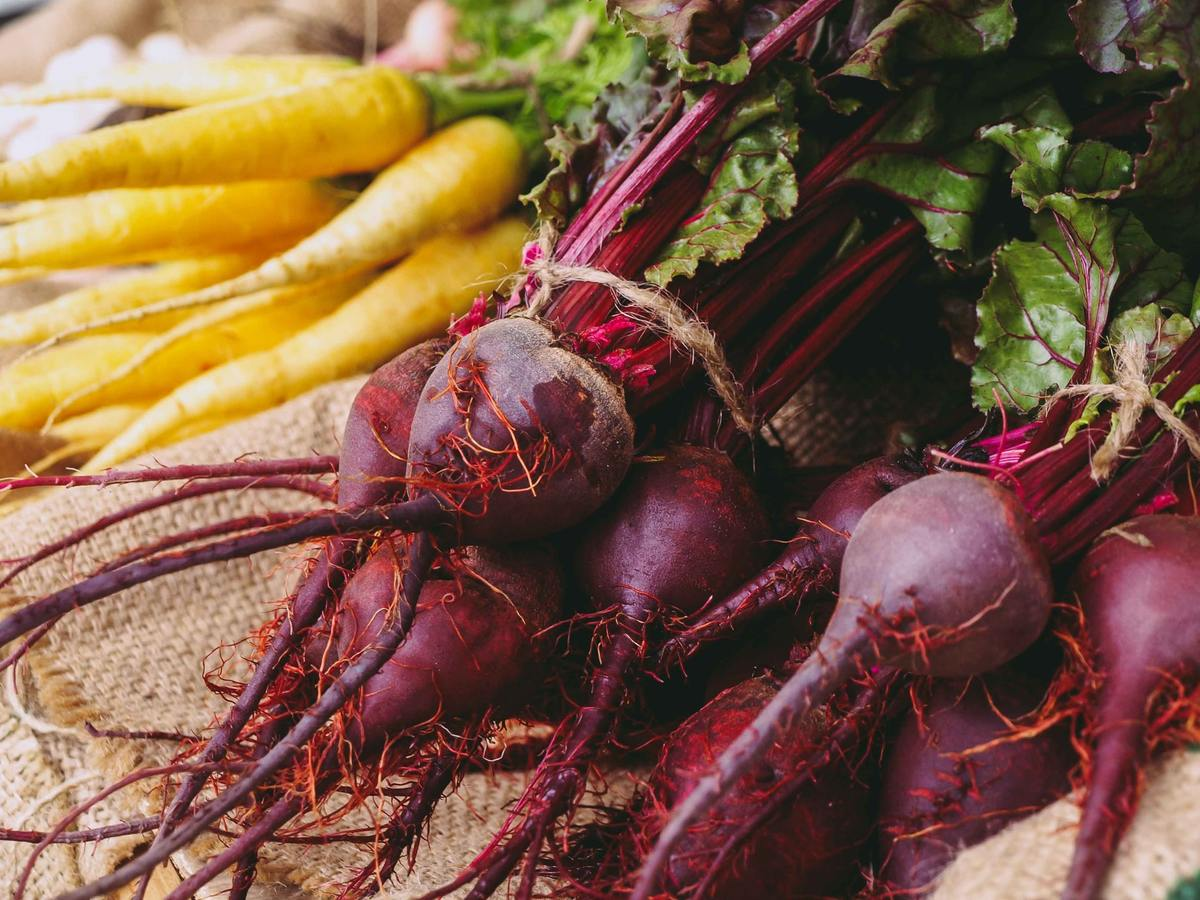 A pile of raw beets lies next to carrots.
