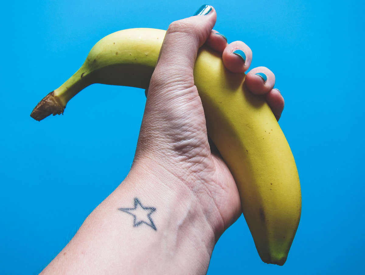 A banana is held against a blue background.