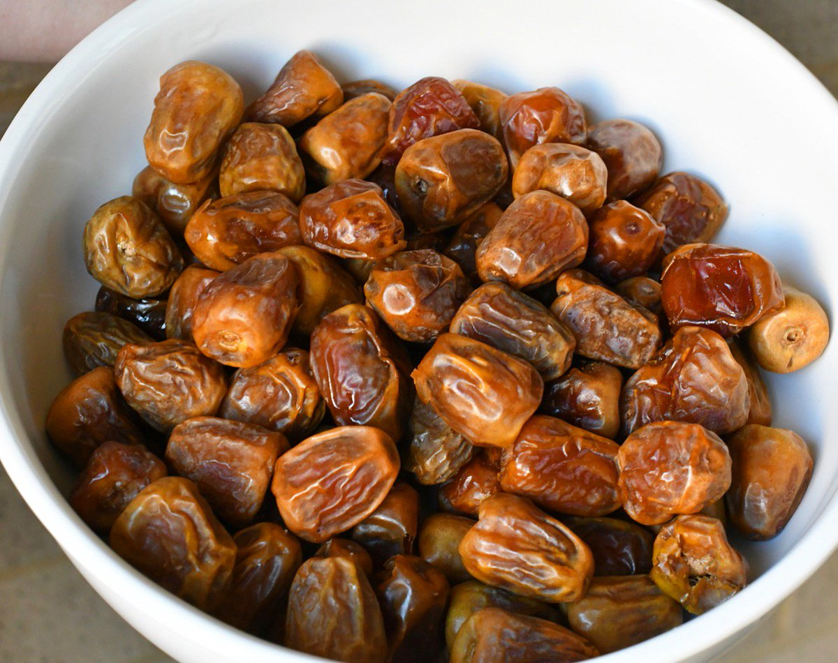 Dates sit in a white bowl.