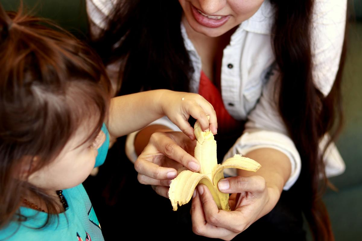 A child takes a piece of banana that a mother is holding.