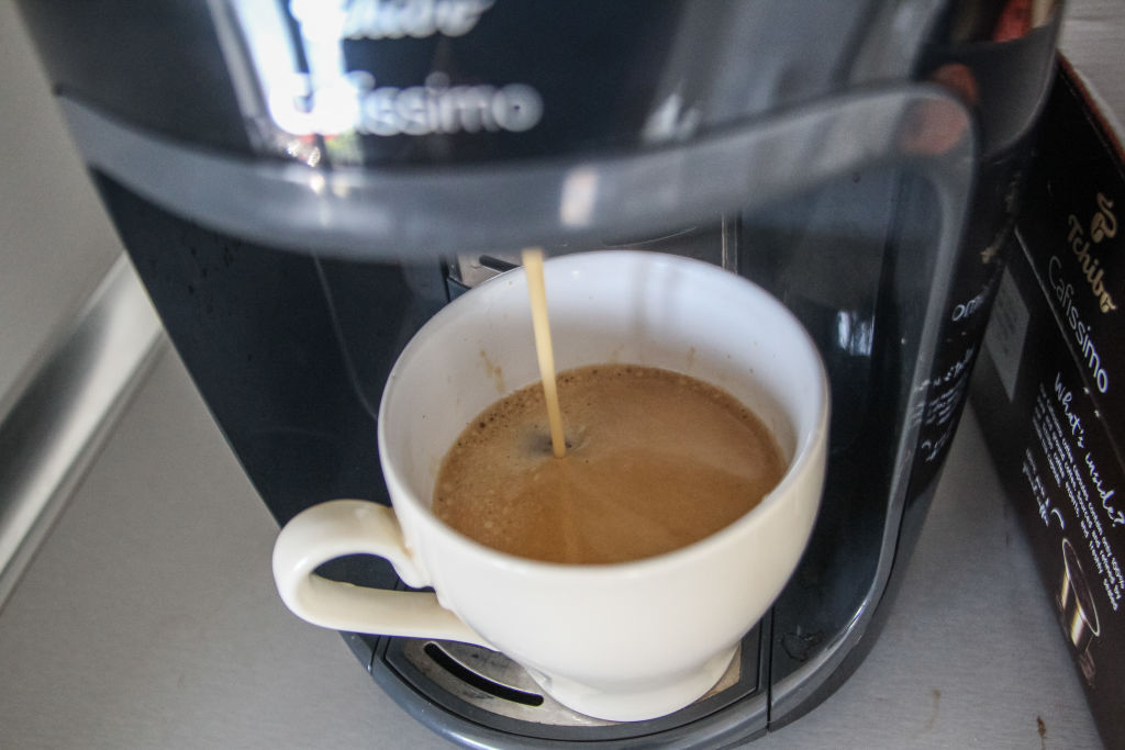 a cup of coffee getting filled by a coffee maker