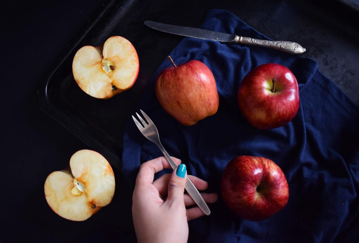 A person holds a fork near cut apples.