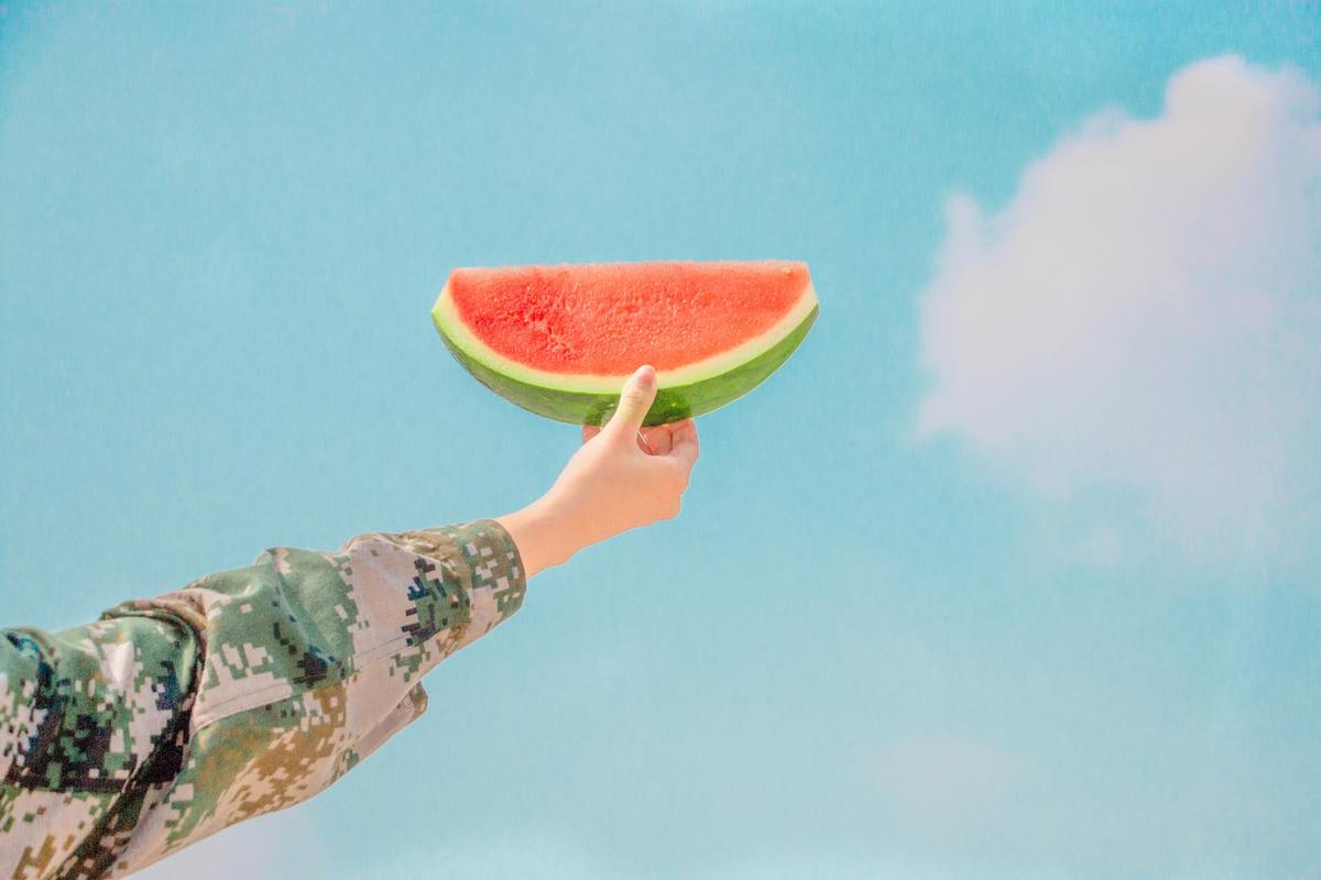 A person holds a wedge of watermelon against the sky.