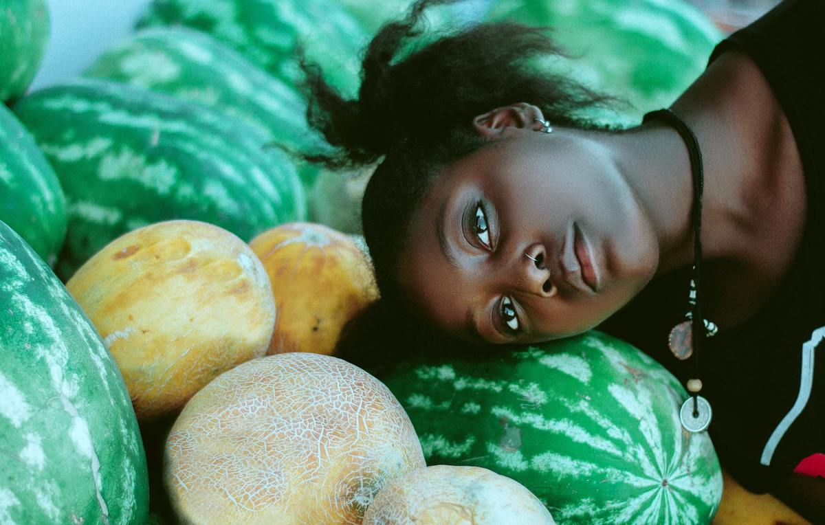 A model poses with her head on a watermelon.