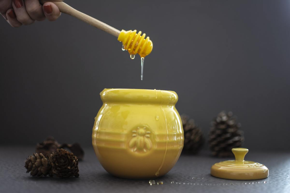 A honey comb drips honey into a yellow pot.