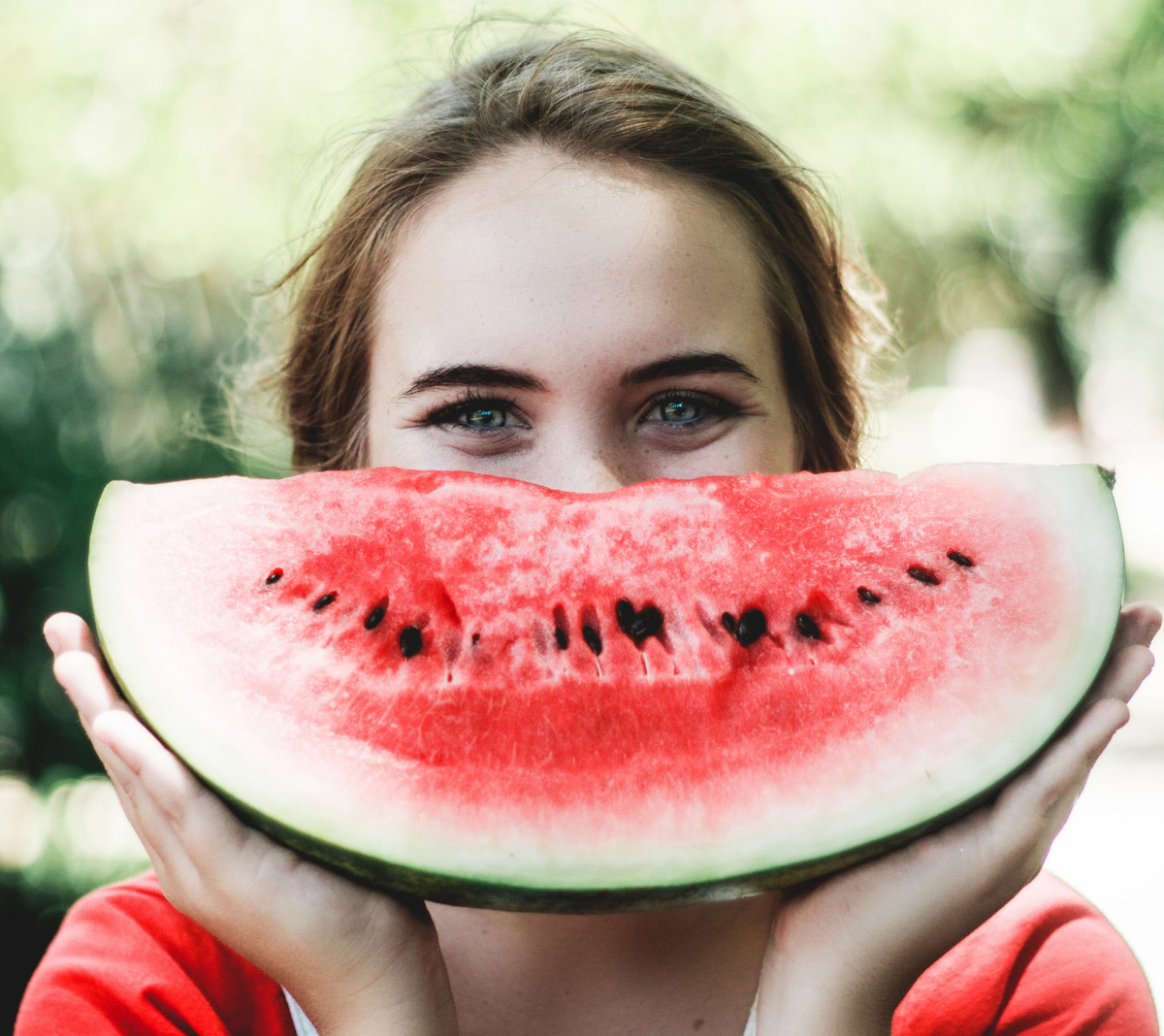 A woman holds up a huge watermelon wedge in front of her face.