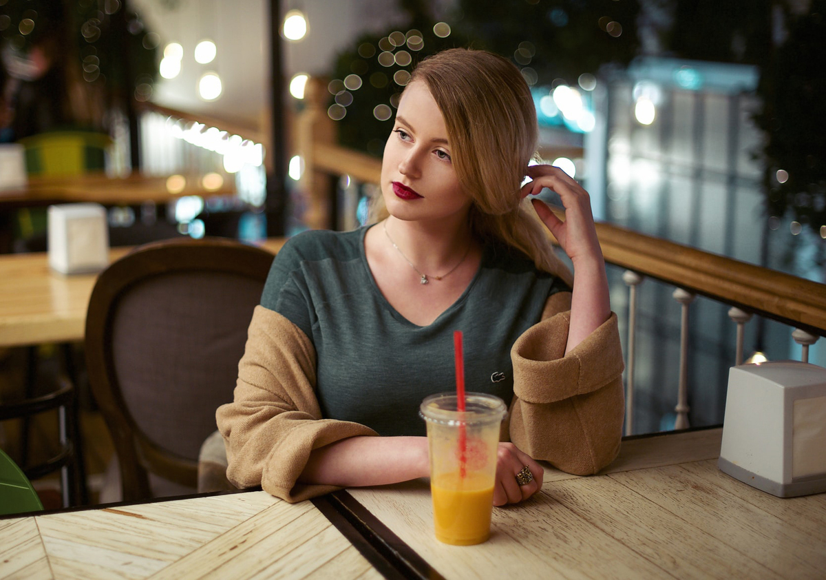 A woman drinks orange juice in a cafe.