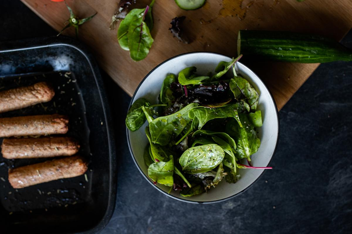 Cooked sausages sit next to spinach and lettuce.