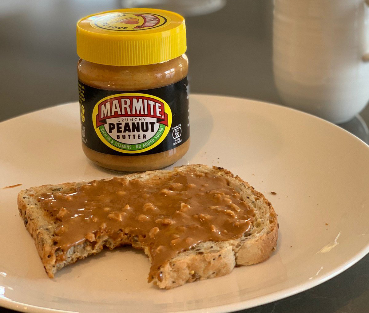 Marmite peanut butter is spread on toast.