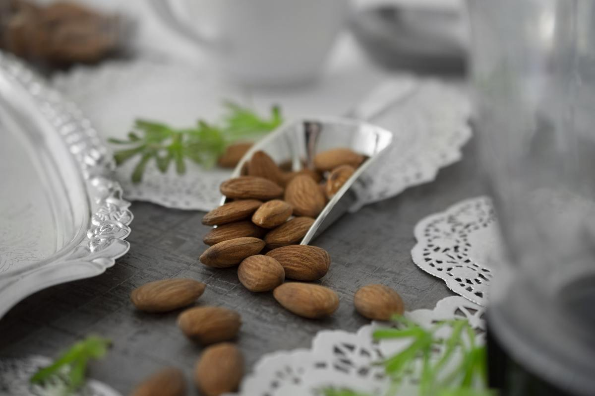 A silver scoop spills almonds on a table.