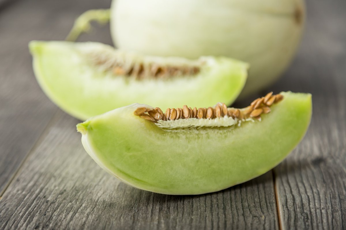 Sliced honeydew rests on a wooden table.