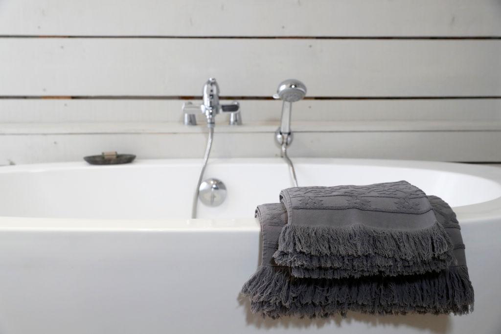 Modern ceramic bathtub with towels