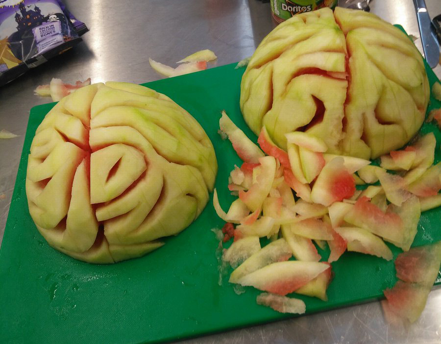 A person carves watermelon into the shape of a brain for a Halloween party.