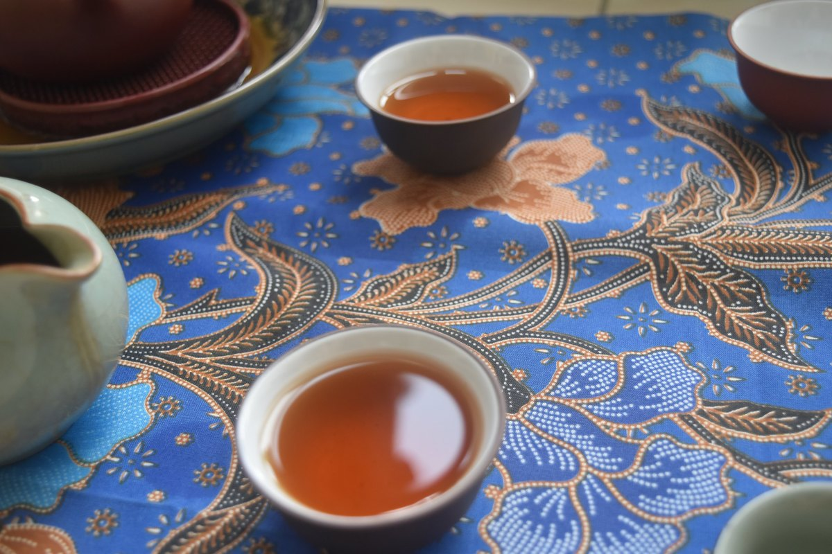 Cups of puerh tea sit on a blue patterned mat.