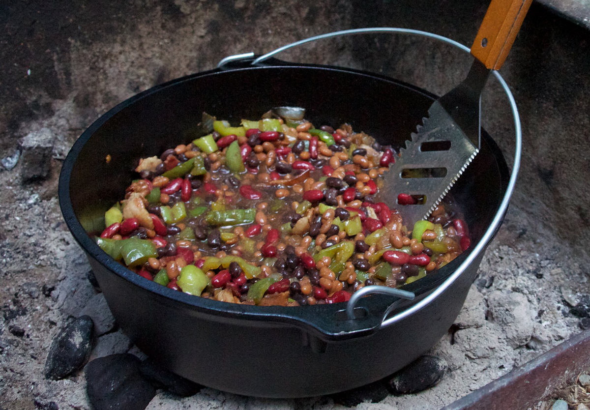 A pot of chili cooks over a campfire.