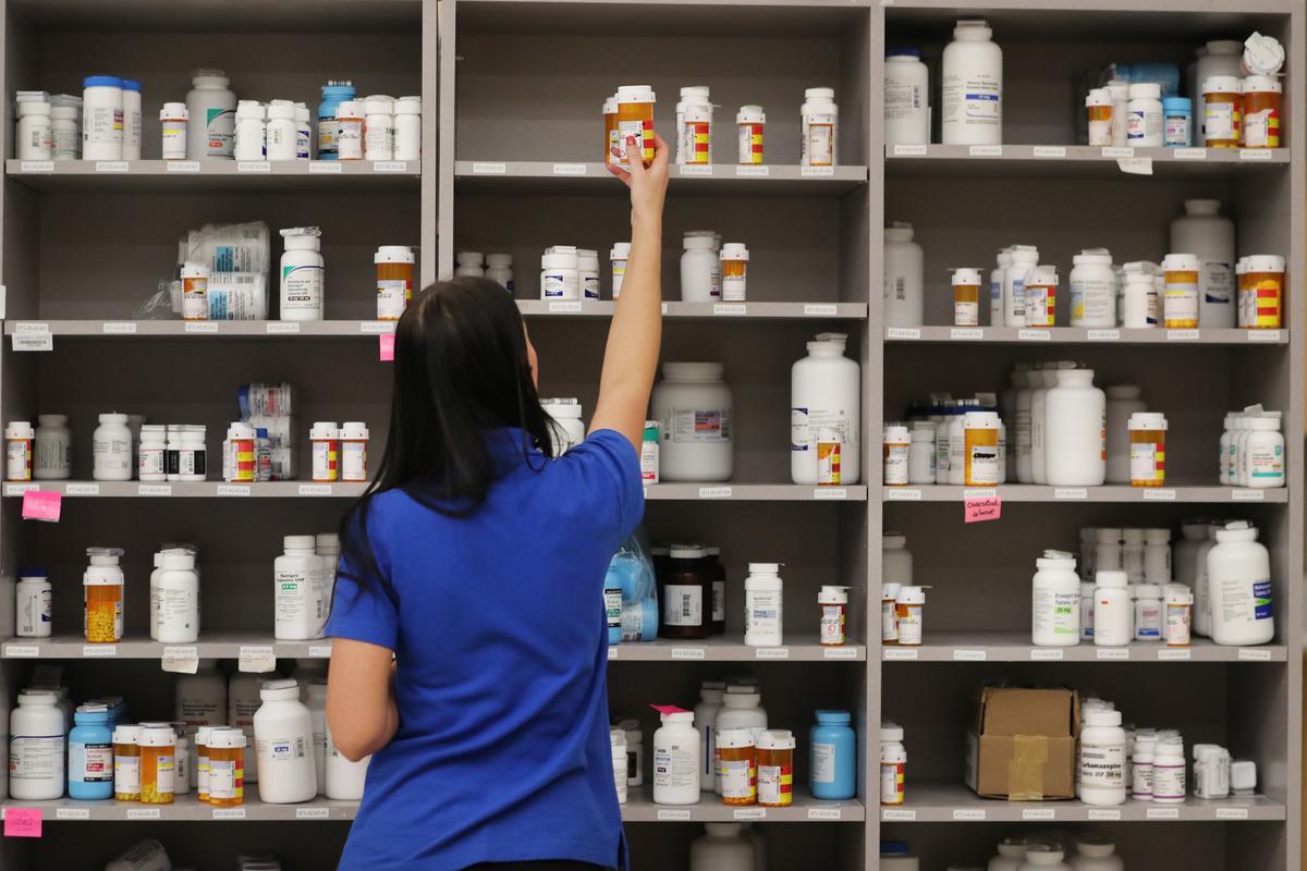 A pharmacy technician grabs a bottle of drugs off a shelf.
