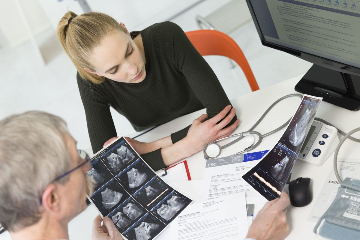 A patient and doctor examine an abdominal ultrasound scan.