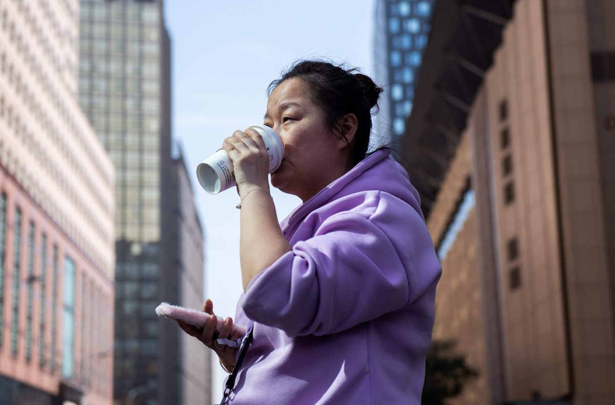A woman drinks a coffee on a street in Beijing.