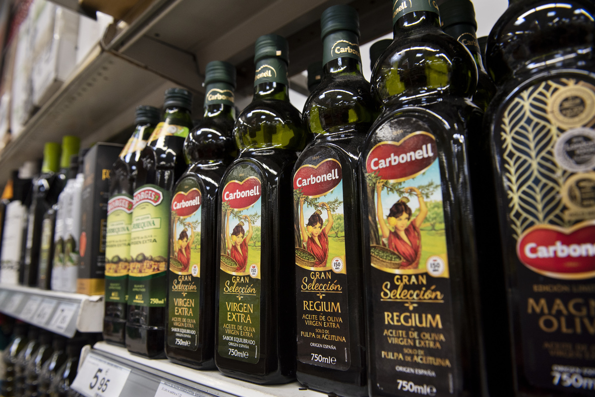 Bottles of olive oil are stacked on a shelf.