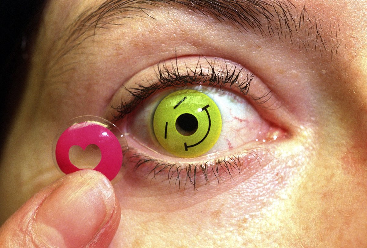 A woman puts in colored contact lenses.